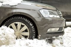 Close-up detail front part of car, wheel, bumper and hood in dee. P snow on blurred winter day background. Transportation, modern lifestyle and parking problems royalty free stock images