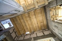Close-up detail of house room interior under construction and renovation. Energy saving walls of hollow foam insulation blocks,. Wooden ceiling beams for roof stock images