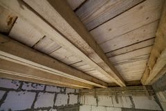 Close-up detail of house room interior under construction and renovation. Energy saving walls of hollow foam insulation blocks,. Wooden ceiling beams for roof royalty free stock image