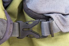 Close-up detail of locked gray convenient secure plastic clasp of yellow backpack. Safety, convenience and reliability of modern a. Ccessories for backpacks stock photography