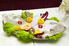 Close Up detail of Metal tray of fish and crustaceans, Oysters,. Shrimp, scallops and ray with lemon salad and flags on toothpick in Italian restaurant dish for Stock Photography