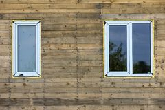 Close-up detail of new narrow plastic vinyl windows installed in. House wall of brown natural wooden planks and boards. Real estate property, comfortable stock photos