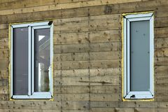 Close-up detail of new narrow plastic vinyl windows installed in. House wall of brown natural wooden planks and boards. Real estate property, comfortable royalty free stock photography