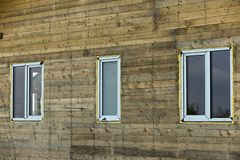 Close-up detail of new narrow plastic vinyl windows installed in. House wall of brown natural wooden planks and boards. Real estate property, comfortable stock photo