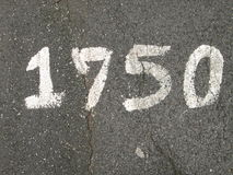 Close up detail of a number painted in white on asphalt Royalty Free Stock Images