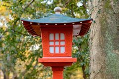 Vintage lantern at Shinto forest shrine. Close-up detail of an ornamental roofed lantern painted colorful red and cyan at a local Shinto forest shrine. Nobeoka royalty free stock photography