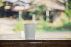 Close up detail of paper coffee cup on wooden pillar with copyspace and green background royalty free stock photography