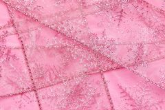 Abstract textured background of pink net ribbon with glitter snowflakes stock photos