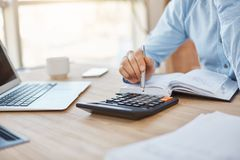 Close up detail of professional serious accountant sitting in light office, checking company finance profits on. Calculator, writing down results in notebook royalty free stock images
