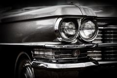 Close up detail of restored classic American car. Focus on headlights. Retro vehicle in black and white royalty free stock photos