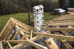 Close-up detail of roof frame of rough wooden lumber beams and chimney made of foam insulation blocks on blurred green background. Building, roofing stock image