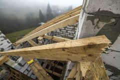 Close-up detail of roof frame of rough wooden lumber beams on walls made of hollow foam insulation blocks on rural landscape. Background. Building, roofing stock photos