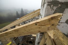 Close-up detail of roof frame of rough wooden lumber beams on walls made of hollow foam insulation blocks on rural landscape. Background. Building, roofing stock photo