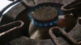 Close up detail shot of old rusty kitchen stove ring switched on fire with lighter flame burning in dangerous gas energy stock footage