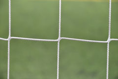 Close up detail of a soccer net against green grass on a cloudy Royalty Free Stock Image