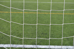 Close up detail of a soccer net against green grass on a cloudy Stock Photos