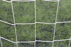 Close up detail of a soccer net against green grass on a cloudy Royalty Free Stock Photos