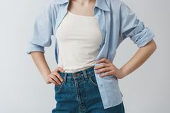 Close up detail of stylish clothes of young female student holding hands on waist, wearing white t-shirt under blue. Shirt and jeans Stock Photo