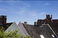 Close up detail of town house rooftops with chimneys against blue sky. stock photography