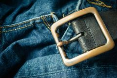 close up detail of an unbuckled leather belt on a faded pair of blue jeans stock photography