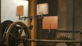 Close up detail view of complicated internal clock mechanism with gearwheels and moving links stock video footage