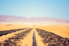 Close up detail view of train tracks leading through the desert near the city of Luderitz in Namibia, Africa. Selective focus on f. Oreground. Mountain range in Royalty Free Stock Photo