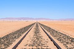 Close up detail view of train tracks leading through the desert near the city of Luderitz in Namibia, Africa. Selective focus on f. Oreground. Mountain range in Stock Photos
