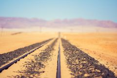 Close up detail view of train tracks leading through the desert near the city of Luderitz in Namibia, Africa. Selective focus on f. Oreground. Mountain range in Stock Photo