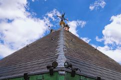 Close-up detail view of weather vane. Abstract outdoor view of the top of an ancient house roof made of grey slates. Blue sky in background. St. Martins stock images