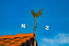 Close-up detail view of weather vane on roof of house.  royalty free stock image