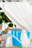 Close-up detail of white sunbeds inside tend by a modern pool Stock Image