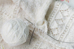 Close up detail of white wool woven handicraft knit baby sweater design texture and clew. Stock Photo