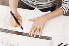 Close up detail of young successful engineer girl in striped top and black jeans, making work at home, working on new. Blueprint with hand and gun Stock Image