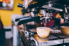 Details of barista preparing fresh espresso on industrial brewing machinery. Close up Details of barista preparing fresh espresso on industrial brewing machinery royalty free stock image