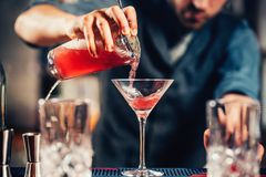 Close up details of barman pouring vodka cosmopolitan cocktail. In martini glass Stock Photos