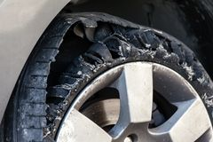 Blown out tire with exploded, shredded and damaged rubber. Close up details of a blown out tire with exploded, shredded and damaged rubber on a modern suv Stock Photo