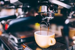 Close up details of brewing machinery pouring and preparing espresso. Cafe shop details Stock Photos