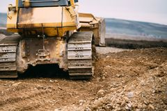 Close up details of bulldozer pushing earth and leveling ground on construction site Royalty Free Stock Images