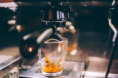 Details of espresso machine pouring and brewing fresh, creamy coffee in local bistro, restaurant or bistro Stock Images