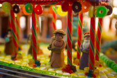 Close-up details of gingerbread Christmas scenery with human fig. Christmas scenery with human figurines dressing up the traditional vintage winter clothes stock photo