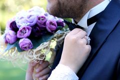 Girl corrects bride groom boutonniere. flowers Advertising. royalty free stock photo
