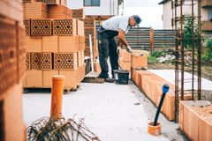 details of industrial bricklayer installing bricks on industrial building, construction site royalty free stock images