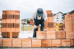 Details of industrial bricklayer installing bricks on construction site stock photo
