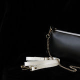 Close-up detal of leather handbag, always classic combination, black and white color with strap and chain. For modern. Pattern, wallpaper or banner design royalty free stock image