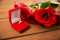 Close up of diamond engagement ring and red roses Stock Images