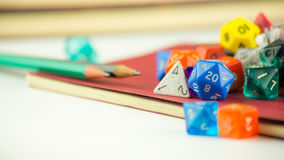 Close up of dice with Pencils on a Notebook. Close up of multicolored dice with Pencils on a red Notebook Stock Photography