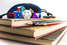 Close up of Dice and Pencils on top of Books. Close up of multicolored Dice with dice bag and Pencils on top of three Books Royalty Free Stock Image