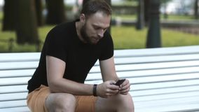 Close-up die aantrekkelijke jonge mensenzitting op een bank in het park glimlachen en een smartphone het gebruiken verzendt sms stock video