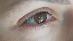 Close-up die bruin vrouwelijk oog openen loenst van het licht stock footage