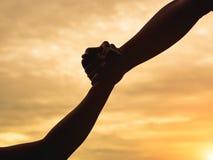 Close-up die handen op de achtergrond van de zonsonderganghemel helpen Redding & Hel stock afbeelding